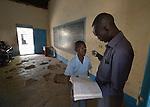 A teacher reviews a student's work at the John Paul II School in Wau, South Sudan.