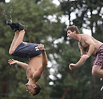 Bobby Nelson (L) performs a front flip as Nelson Merritt (R) jumps from a bridge into the Burley Lagoon in Olalla, Washington on 1 January  2010. Over 300 hardy participants  braved the chilly lagoon waters to join in on the annual New Year's Day Tradition.  Jim Bryant Photo. ©2010. ALL RIGHTS RESERVED.