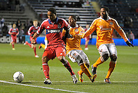 Chicago forward Sherjill MacDonald (7) plays the ball while being defended by Houston's Corey Ashe (26) and Jermaine Taylor (4).  The Houston Dynamo defeated the Chicago Fire 2-1 in the Eastern Conference play-in game for the MLS Playoffs at Toyota Park in Bridgeview, IL on October 31, 2012.