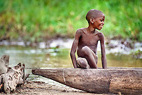 Boy in hand carved canoe, Okavango Delta, Botswana