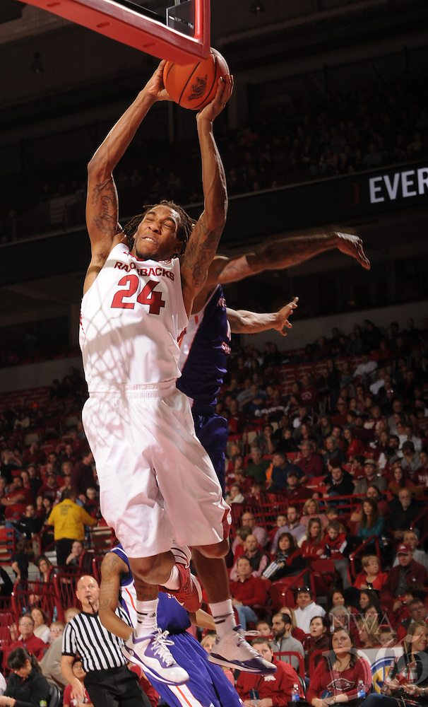 NWA Media/ANDY SHUPE - Arkansas' Michael Qualls (24) reaches to dunk the ball past a Northwestern State defender during the first half Sunday, Dec. 28, 2014, in Bud Walton Arena in Fayetteville.