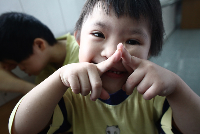 A young Agent Orange victim smiles as his picture is made in the Agent Orange children's ward of Tu Du Hospital in Ho Chi Minh City, Vietnam. About 500 of the 60,000 children delivered each year at the maternity hospital, Vietnam's largest, are born with deformities, some of them because of Agent Orange, according to doctors. May 1, 2013.