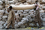 Following an October 8, 2005, earthquake in northern Pakistan, Church World Service/Action by Churches Together responded quickly to the needs of thousands of affected families. Here survivors of the quake carry relief supplies provided by CWS/ACT.