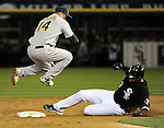 CHICAGO - APRIL 12:  Mark Ellis #14 of the Oakland Athletics leaps over the sliding Mark Teahen #23 of the Chicago White Sox to turn a double play on April 12, 2011 at U.S. Cellular Field in Chicago, Illinois.  The White Sox defeated the Athletics 6-5.  (Photo by Ron Vesely)  Subject:  Mark Ellis;Mark Teahen