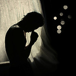 A male figure praying in silhouette by window