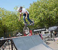 """BMX bike demo at the AfroPunk Festival in Commodore Barry Park in Brooklyn in New York on Sunday, August 26, 2012. The festival in the neighborhood of Fort Greene bills itself as the """"other black experience"""" and blends the black punk and hardcore punk scenes. There is also a diverse aspect combining other minority groups, all dressed in their fashionable punk ensembles. (© Richard B. Levine)"""