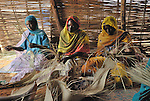 Displaced women weaving mats in a livelihood program  in the Dereig Camp for internally displaced persons.