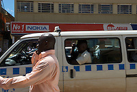 A man talking on his mobile handset is overtaken by a Matatu minibus-taxi on Kampala Road, the electronics district of the Ugandan capital.