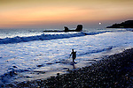 Surfer walks along El Tunco beach on the Pacific in El Salvador.  El Tunco is named after the rock formation seen in the photograph.