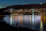 The lights of West Vancouver and the Lions Gate Bridge reflect in Burrard Inlet at Stanley Park - Vancouver, British Columbia, Canada
