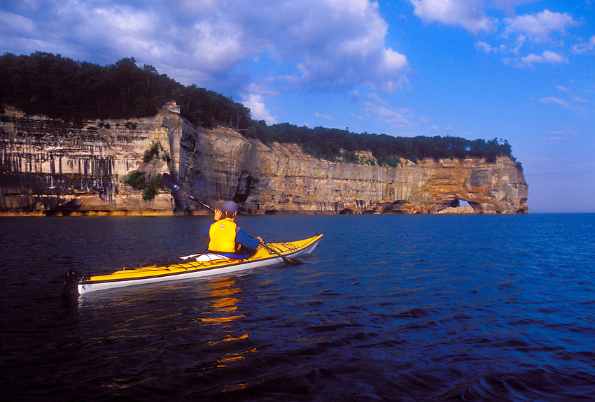 A sea kayaker paddles towards Grand Portal Point from the east in the Pictured Rocks National Lakeshore near Munising, Mich.