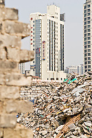 old wall and piles of rubble from demolished building with hotel in background, Shanghai, China