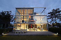The exterior of architect, Hans van Heeswijk's, impressive contemporary house in Amsterdam, where triple-height windows and virtually no walls creates a wonderful sense of space and light. The house is seen at night.