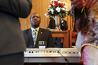 Pastor Peter Chege feels the music during Sunday service at The Africa Lighthouse Baptist Temple near Stony Point in Albemarle County, VA. The small 10 family congregation is made up of African refugees and immigrants who's service is spoken in Swahili and translated into English. They've just signed a rent-own lease for a small church after meeting for three years at a local school. Photo/The Daily Progress/Andrew Shurtleff