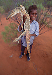 An aboriginal boy with a sand goanna, Tjuwanpa Outstation, Australia