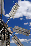 Ancient wooden windmill blades over blue cloudy sky