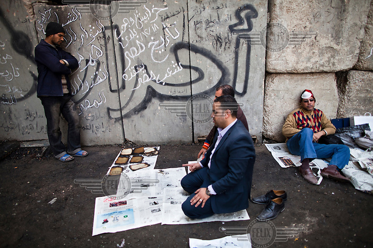 Volunteers take a break to pray after helping remove theburnt remains of books from the Institute of Egypt. The building caught fire during clashes between protesters and the Egyptian military. The building contained some 192,000 books, journals and writings, some dating back to the 16th Century, most have been destroyed.