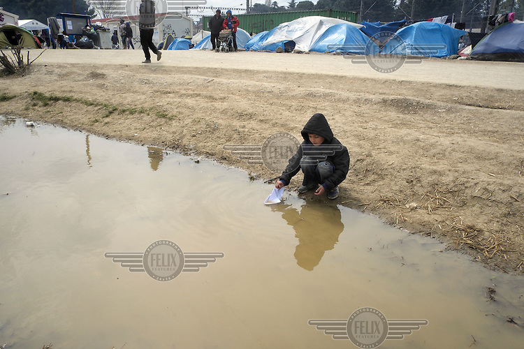 A refugee boy plays with a paper boat in a rain puddle at an unofficial migrant's camp on the Macedonian border.