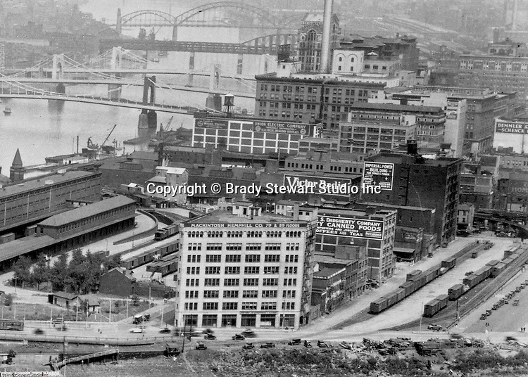 Pittsburgh PA:  View of the Point Buildings and railroad yards in 1928.  In the background are the new 7th & 9th Street bridges;  self-anchored suspension bridges spanning the Allegheny River.  Company signs are the city buildings include:  Victor Radio, Demmler & Schenck, Mackintosh Hemphill Company, Daugherty Company Canned Foods, Imperial Power Building, Union Electric Company, & General Electric Wiring Systems