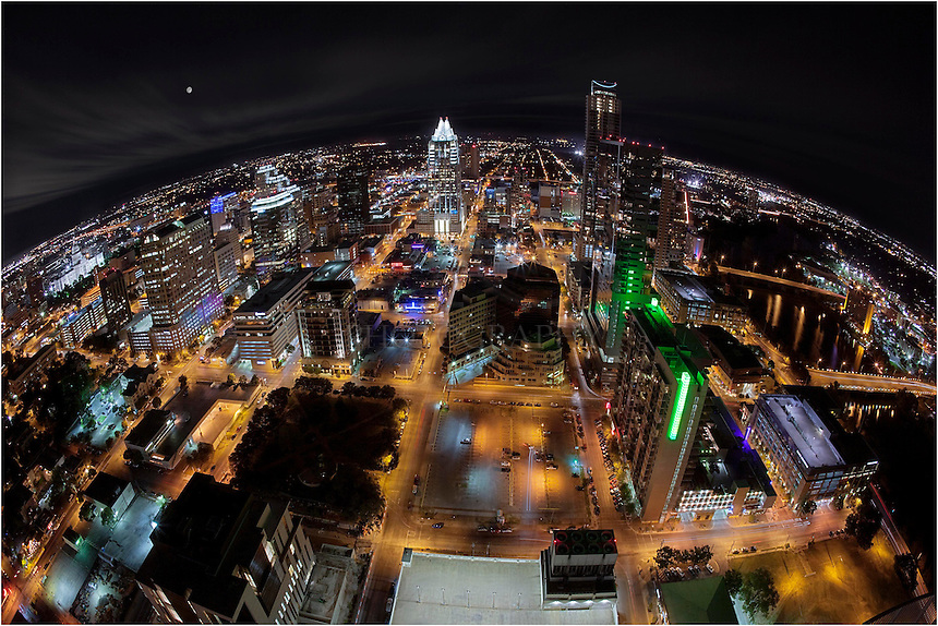 This image of downtown Austin was taken from 44 stories above Austin. The fisheye lens gives it the curvature to encompass a 180 degree view. Directly in view is the Frost Tower, an Austin icon. To the right is Lady Bird Lake, also known as Town lake, and to the left is the Texas Capitol.