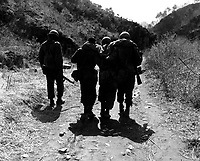 Buddies aid wounded man of 24th Inf. Regt., after a battle 10 miles south of Chorwon, Korea.  April 22, 1951.  Cpl. Tom Nebbia. (Army)<br /> NARA FILE #:  111-SC-365537<br /> WAR &amp; CONFLICT BOOK #:  1446