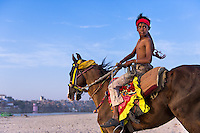 Man riding horse on the beach in Varanasi, Uttar Pradesh, India