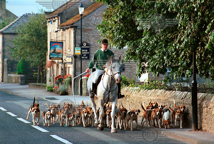 Clive Richardson guides his horse and hounds along Horby High Street.