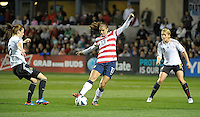 US forward Alex Morgan (13) plays the ball in between Germany's Verena Faibt (15) and Saskia Bartusiak (3).  The U.S. Women's National Team tied Germany 1-1 in a friendly at Toyota Park in Bridgeview, IL on October 20, 2012.