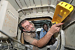 Stephen Quigg, a United Methodist missionary, installing an emergency location transmitter in a plane belonging to Wings of Caring Aviation in Kananga, Congo. The program is sponsored by the United Methodist Church. The Kananga-based pilot in the background is Jacques Umembudi Akasa.