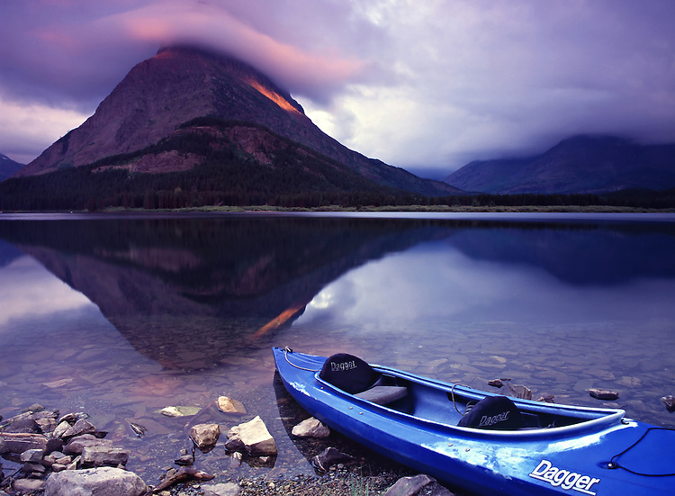 A single kayak rests along the shores of Swiftcurrent Lake in the Many Glacier Valley in Glacier National Park, Montana