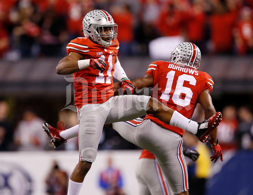 Ohio State Buckeyes defensive back Vonn Bell (11) celebrates an interception with defensive back Cam Burrows (16) during the first quarter of the Big Ten Championship game against the Wisconsin Badgers at Lucas Oil Stadium in Indianapolis on Dec. 6, 2014. (Adam Cairns / The Columbus Dispatch)