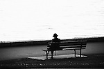 A woman sitting alone on a park bench, with the ocean in the background.