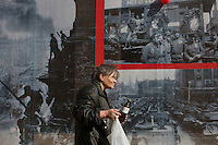 Moscow, Russia, 07/05/2010..A homeless woman walks past giant World War Two photographs, part of a display near Red Square in the lead-up to the forthcoming May 9 Victory Day parade, scheduled to be the largest for many years.