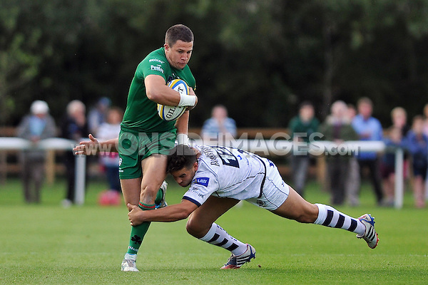 Fergus Mulchrone is tackled by Ben Mosses. Pre-season friendly match, between London Irish and Bristol Rugby on August 22, 2014 at Hazelwood in Middlesex, England. Photo by: Patrick Khachfe / JMP