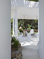 View between columns on the whitewashed terrace towards the outdoor dining area