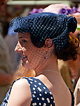 Woman wearing and polkadot dress and a navy vintage hat with netting on it in the Easter Parade on Fifth Avenue in New York City