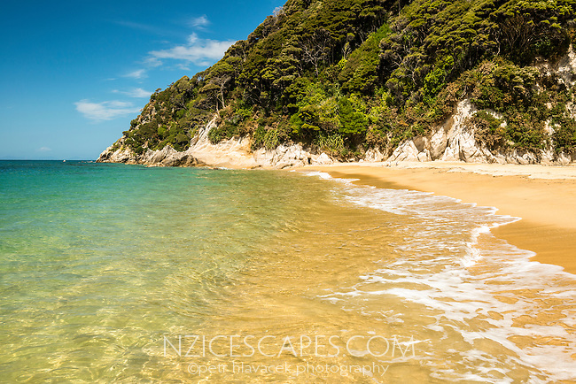 Crystal clear waters and golden sand of Anatakapau Bay on Abel Tasman Coast Track, Abel Tasman National Park, Nelson Region, South Island, New Zealand