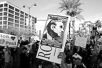Mesa, Arizona. February 23, 2012 - As Republican candidates debated in the Mesa Arts Center, protesters including undocumented students, tea partiers, occupy movement members and Syrian president opponents, shouted slogans and held up signs and placards outside. In this photograph, a political campaign poster is raised above the crowd during the demonstrations. Ron Paul's followers had a strong presence outside the complex where the Republican presidential debate took place. Photo by Eduardo Barraza © 2012