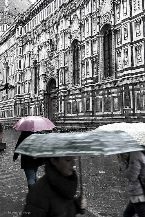 People with colorful umbrellas pass in front of the Duomo in Florence, Italy