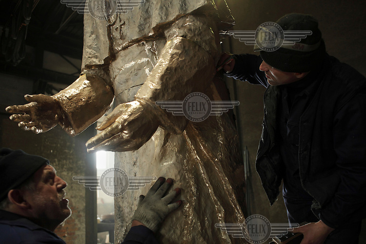 Wieslaw Bochynski and Kazimierz Janicki, workers at the GZUT factory that specialises in making bronze monuments, piece together a statue of Pope John Paul II.