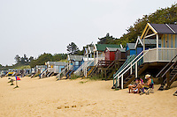 Couple sit outside beach hut in Wells, Norfolk, United Kingdom