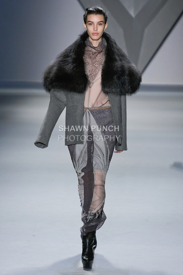 Kate King walks runway in a grey mélange wool long sleeve jacket with oversized charcoal raccoon collar over grey vault print silk chiffon sleeveless gown with cowl neck and net lace insets, and grey rib knit bermuda short, from the Vera Wang Fall 2012 Vis-a-gris collection, during Mercedes-Benz Fashion Week Fall 2012 in New York.