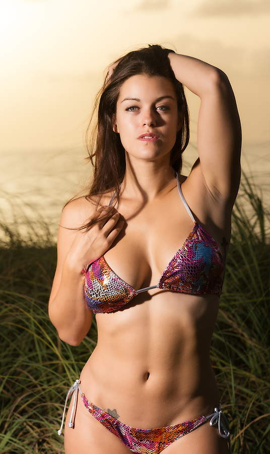 Beautiful caucasian woman in bikini at the beach during sunrise.