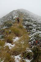 Jente går langs snødekt åsrygg ---- Girl hiking along snow covered hill
