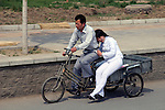 Asia, China, Beijing. Couple on a pedicab in the streets of Beijing.
