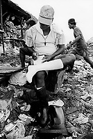 Philippines. Luzon Region. Manila. Tondo area. Smokey mountain is a rubbish dump. Life on a garbage heap. Scavengers on dumpsite. A man, seated on a wodden box, writes in a note book. He wears a pair of shorts, clean white socks, has taken off his black plastic boot and has a key around his neck. © 1992 Didier Ruef ..
