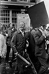 National Front march Lewisham, South London England 1977. NF member carries wooden weapons. They are being attacked by extreme left groups. The police protect them.