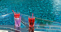 Cocktail glasses on table by pool