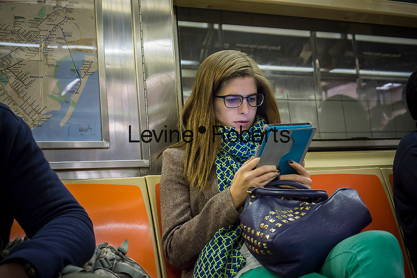 An Apple iPad user reads during her subway ride in New York on Monday, November 4, 2013. (© Richard B. Levine)
