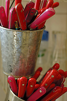 Brightly colored cutlery drying in metal containers.
